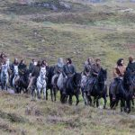 Cast of Outlaw King riding through Glencoe